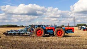 Una gama del vintage triplicó el tractor que tiraba de un arado fotografía de archivo libre de regalías