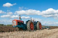 Una gama del vintage triplicó el tractor que tiraba de un arado fotos de archivo libres de regalías