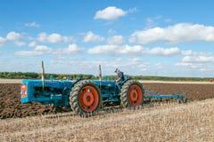 Una gama del vintage triplicó el tractor que tiraba de un arado fotos de archivo