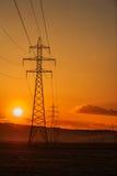 Poste ad alta tensione al tramonto Fotografia Stock