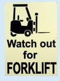 Una gente de información de la señal de peligro a cuidar porque las carretillas elevadoras son en funcionamiento en el área Imágenes de archivo libres de regalías