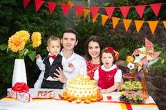 Una gente de la familia de cuatro miembros se está sentando en una tabla festiva con una torta y los regalos Mún día de fiesta ab fotografía de archivo libre de regalías