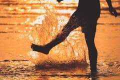 Una gente que camina en el chapoteo de la playa y del agua en tiempo de la puesta del sol imagen de archivo libre de regalías