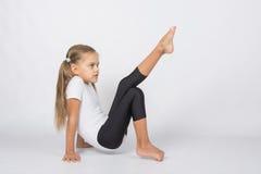 Una ginnasta d'aspirazione che prova a tirare il suo piede sinistro che riposa sulle mani e sulle dita del piede destro Immagini Stock Libere da Diritti
