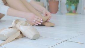 Una giovane ballerina impasta e fa un massaggio del piede dopo una prestazione o l'addestramento nello studio archivi video