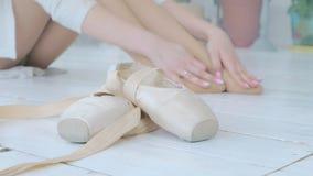 Una giovane ballerina impasta e fa un massaggio del piede dopo una prestazione o l'addestramento nello studio video d archivio