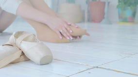 Una giovane ballerina impasta e fa un massaggio del piede dopo una prestazione o l'addestramento nello studio stock footage
