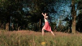 Una giovane bella donna cammina felicemente nel legno, toccando il suo vestito, saltando e sollevando le sue mani per toccare video d archivio