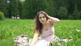 Una giovane bella donna che si siede sul plaid su erba in parco video d archivio