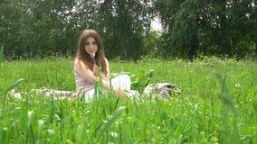 Una giovane bella donna che si siede sul plaid su erba in parco archivi video