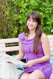 Una giovane bella donna si siede in una sosta su un banco Fotografia Stock