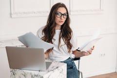 Una giovane bella donna sta facendo penetrare un ufficio moderno occupato con lavoro di ufficio Si siede ad una tavola con un tac Immagine Stock Libera da Diritti