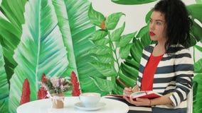 Una giovane, bella donna in un vestito a strisce fa le note in un taccuino stock footage