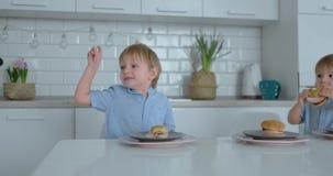 Una giovane bella madre in un vestito bianco con due bambini è sorridente e mangiante gli hamburger freschi nella sua cucina fel video d archivio