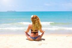 Una giovane, bella ragazza con capelli rossi, in un bikini yoga di pratiche sul mare bianco del turchese e della sabbia fotografie stock libere da diritti