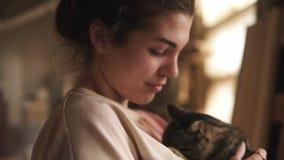 Una giovane, bella ragazza sta giocando con un gatto delicato e grigio Lui che graffia le sue orecchie, carezze felice dell'inter video d archivio