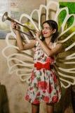 Una giovane bella ragazza sta stando con una tromba in sua mano Immagini Stock Libere da Diritti