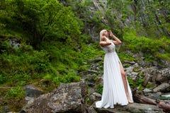 Una giovane condizione bionda della ragazza in un mezzo giro, raddrizzante capelli in un vestito dal boudoir nelle montagne contr fotografia stock libera da diritti
