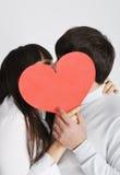 Una giovane coppia che bacia dietro il simbolo di amore Fotografia Stock