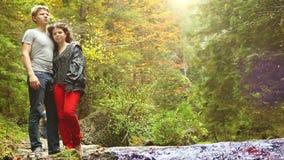 Una giovane coppia che sta vicino all'insenatura della foresta che parla allegramente stock footage
