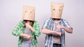 Una giovane coppia con i sacchi di carta sulle loro teste è felice e dancing archivi video