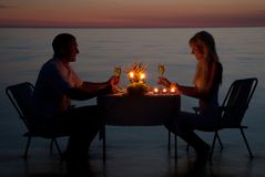 Una giovane coppia divide un pranzo romantico con le candele sulla spiaggia Immagini Stock