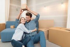 Una giovane coppia durante il movimento verso un nuovo appartamento Persone appena sposate commoventi ad alloggi nuovi Fotografia Stock
