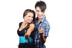 Una giovane coppia felice che mostra i pollici su. Fotografie Stock
