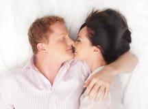 Una giovane coppia felice sopra priorità bassa bianca Fotografia Stock
