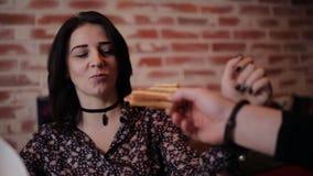 Una giovane coppia incatenata insieme dalle manette fa colazione nel caffè archivi video