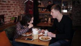Una giovane coppia incatenata insieme dalle manette fa colazione nel caffè video d archivio