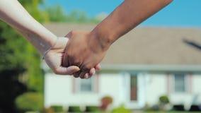 Una giovane coppia prende le mani di ciascuno contro il contesto della loro nuova casa di sogno Concetto d'acquisto del bene immo immagine stock libera da diritti
