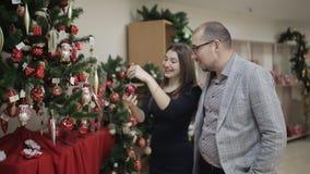 Una giovane coppia prepara per il Natale, sceglie le decorazioni di Natale nel supermercato Una donna che considera il Natale archivi video