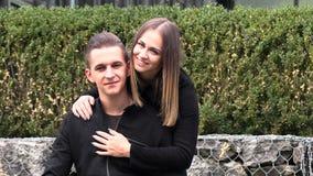 Una giovane coppia si siede su un copriletto bianco nel parco di autunno stock footage