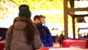 Una giovane coppia sorridente si incontra sulla pista di pattinaggio e sull'abbracciare di pattinaggio su ghiaccio archivi video