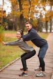 Una giovane coppia sta preparandosi in un parco di autunno Il tipo contribuisce a fare i pendii della ragazza immagini stock