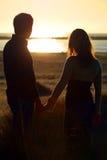 Una giovane coppia sulle mani della holding della spiaggia Fotografia Stock