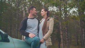 Una giovane coppia - un tipo e una ragazza sono stare, appoggiantesi un'automobile nella foresta che baciano e che abbracciano archivi video