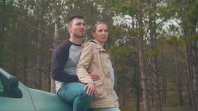 Una giovane coppia - un tipo e una ragazza sono stare, appoggiantesi un'automobile nella foresta che stanno parlando stock footage