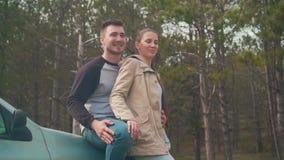 Una giovane coppia - un tipo e una ragazza sono stare, appoggiantesi un'automobile nella foresta che stanno sorridendo e che parl video d archivio