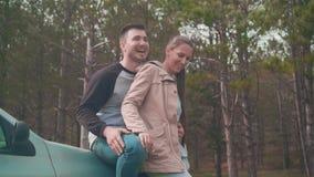 Una giovane coppia - un tipo e una ragazza sono stare, appoggiantesi un'automobile nella foresta che stanno sorridendo e che ride stock footage