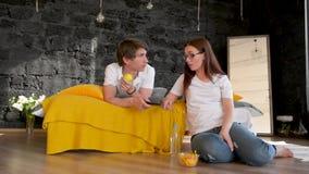 Una giovane coppia, un tipo e una ragazza, bugia su un letto a casa, orologio TV, giurano, non possono decidere che cosa guardera video d archivio
