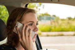 Una giovane donna è sul telefono mentre guida ed è distratta immagine stock
