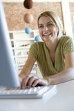 Una giovane donna al suo calcolatore Fotografia Stock Libera da Diritti