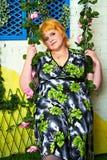 Una giovane donna allegra del giorno soleggiato con en dorata su un'oscillazione si è intrecciata con i fiori rosa in un vestito l Fotografie Stock