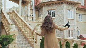 Una giovane donna attraente cammina attraverso il castello, ammira le scale antiche e le torri, indossa i vestiti alla moda, dura video d archivio