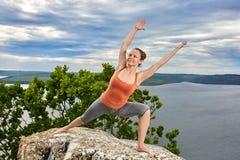 Una giovane donna attraente che fa una posa di yoga per equilibrio sulla roccia Immagine Stock