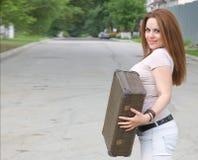 Una giovane donna attraente con una vecchia valigia sulla via Fotografie Stock