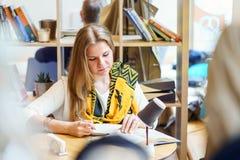 Una giovane donna attraente europea è libro di lettura e scrive una certa cosa in taccuino dalla penna sulla tavola dentro il caf Immagini Stock Libere da Diritti