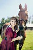 Una giovane donna attraente in un vestito rosso sta tenendo un cavallo marrone fotografia stock